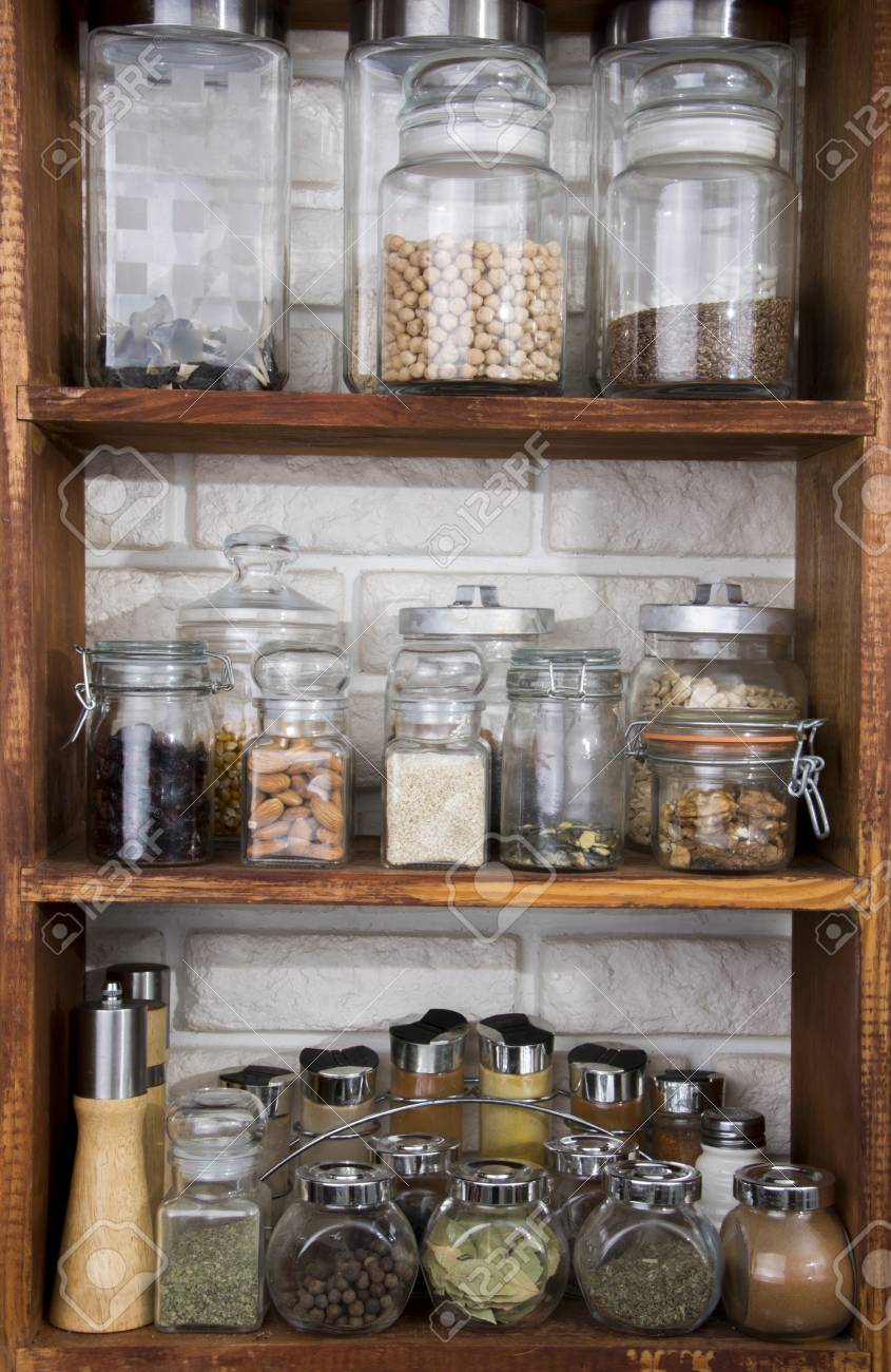 Jars with nuts, dried fruits, spices, herbs and others on kitchen shelves - 60070017