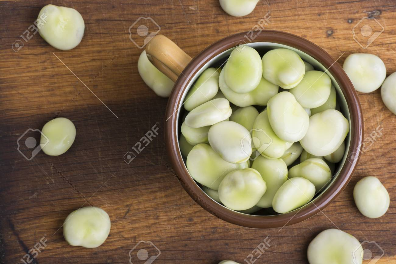 Fresh broad beans in bowl on wooden board - 60697574
