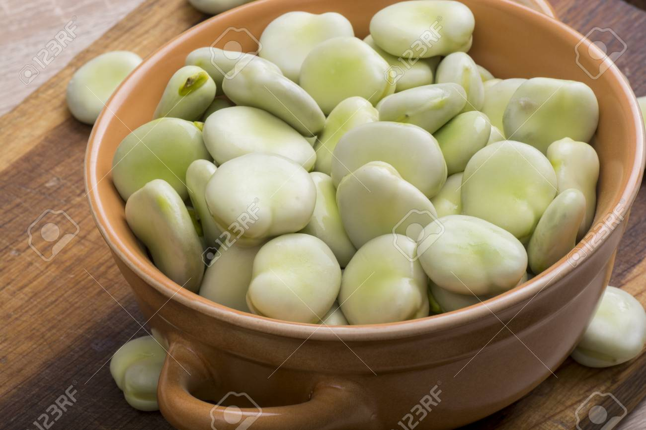 Fresh broad beans in bowl on wooden board - 60697577