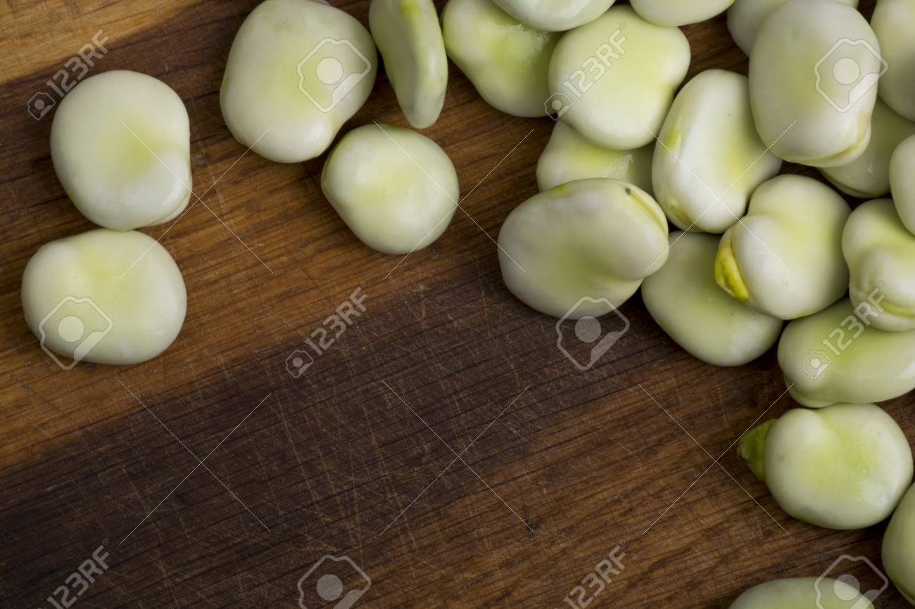 Fresh broad beans on wooden board - 60747237