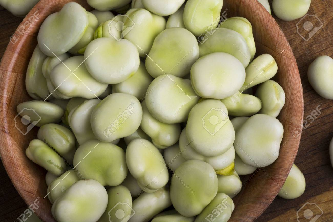 Fresh broad beans in bowl on wooden board - 60747630