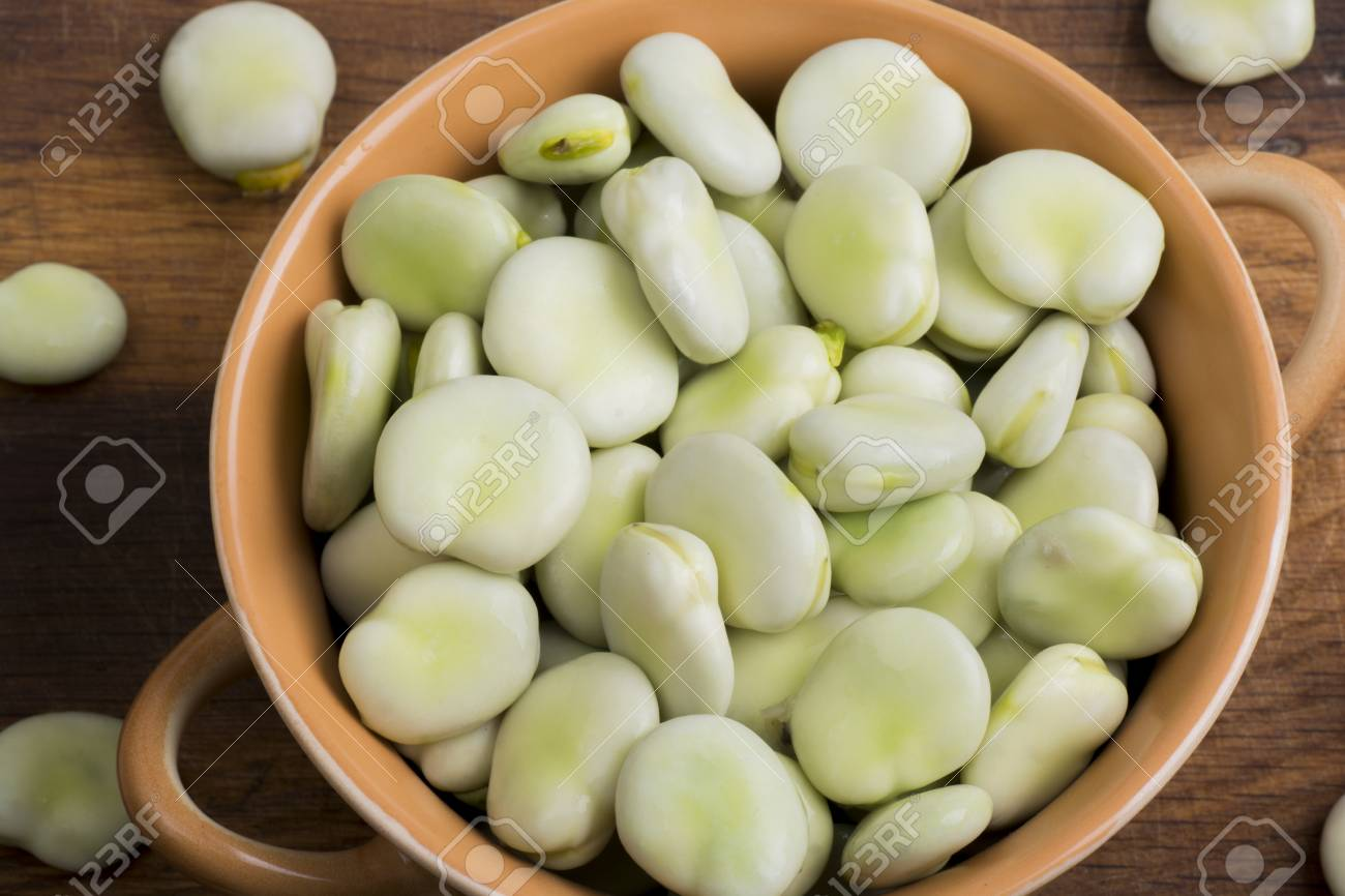 Fresh broad beans in bowl on wooden board - 60747629