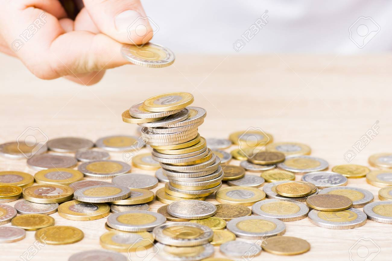 Man stacking coins on table - 64464833