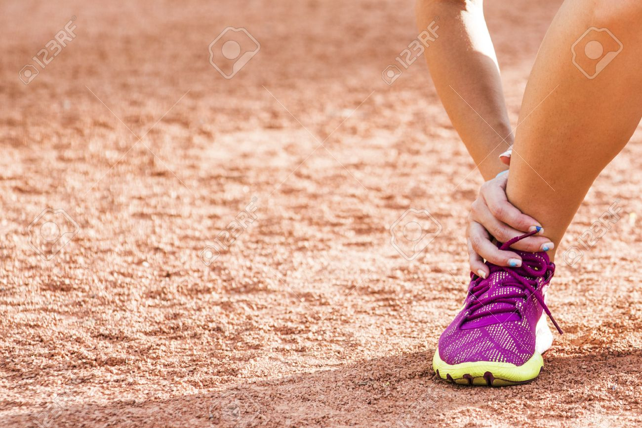 Running sport injury - twisted broken ankle. Female athlete runner touching foot in pain due to sprained ankle. Banque d'images - 41559452