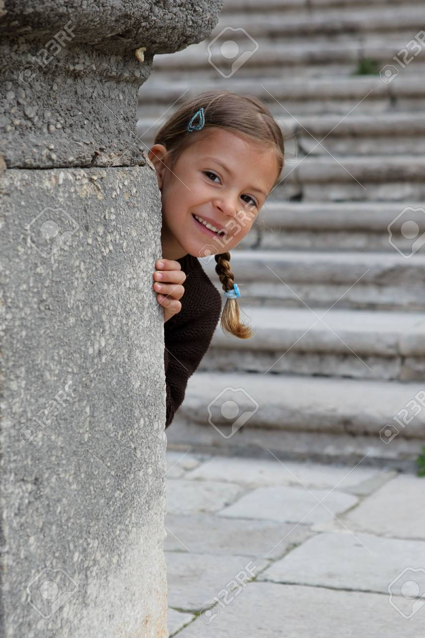 A young girl enjoys playing peek a boo from behind a pillar Stock Photo - 6713288