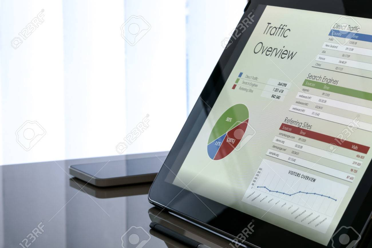 Charts and data on the tablet screen with smartphone next to the window at the office - 70928654
