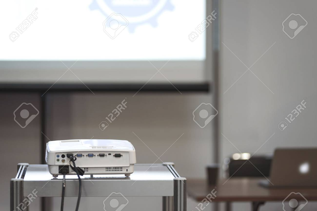 White multimedia projector in a conference room with blured projection screen and a lecturer desk on the background (reduced tone) - 73046891