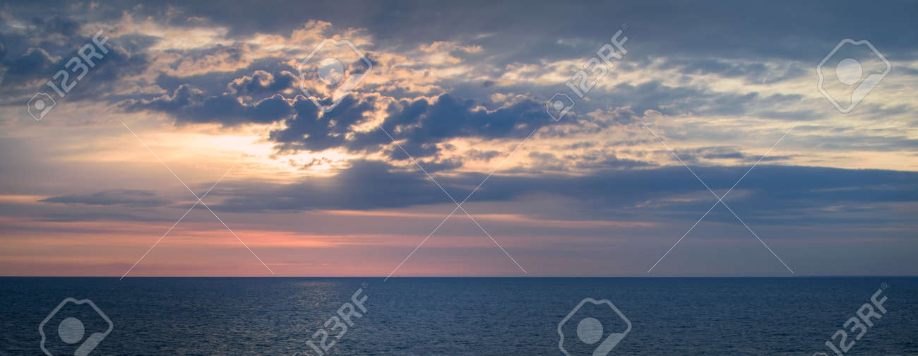 Panoramic view of a picturesque and dramatic sunrise sky over a vast and calm ocean. - 166597212