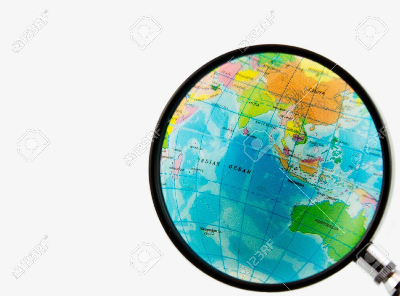 A magnifying glass view of a small colored globe isolated on a white background Stock Photo - 8017270