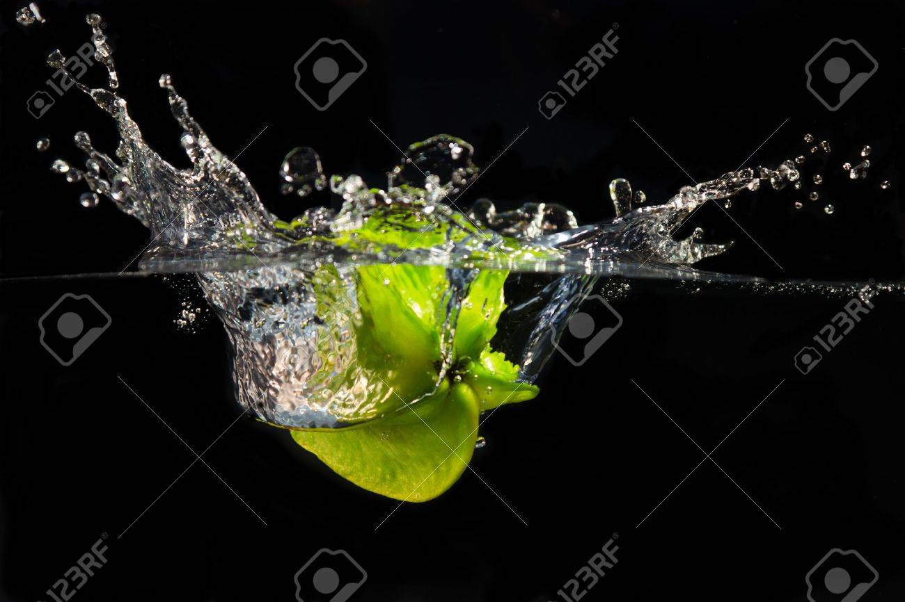 A falling star fruit plunges into the water creating a large splash Stock Photo - 8729366