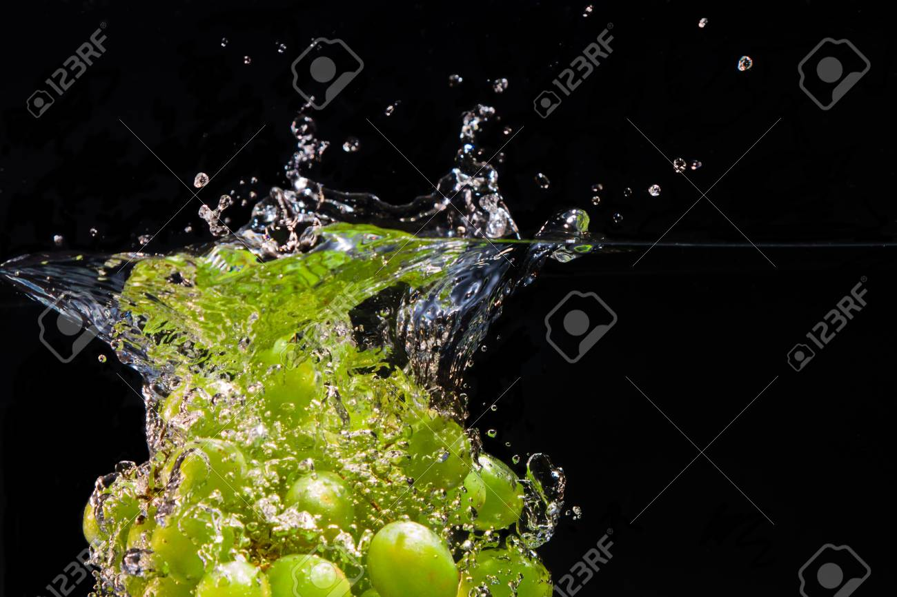 A bunch of grapes dropped into water creates sparkling splashes of droplets Stock Photo - 8729367