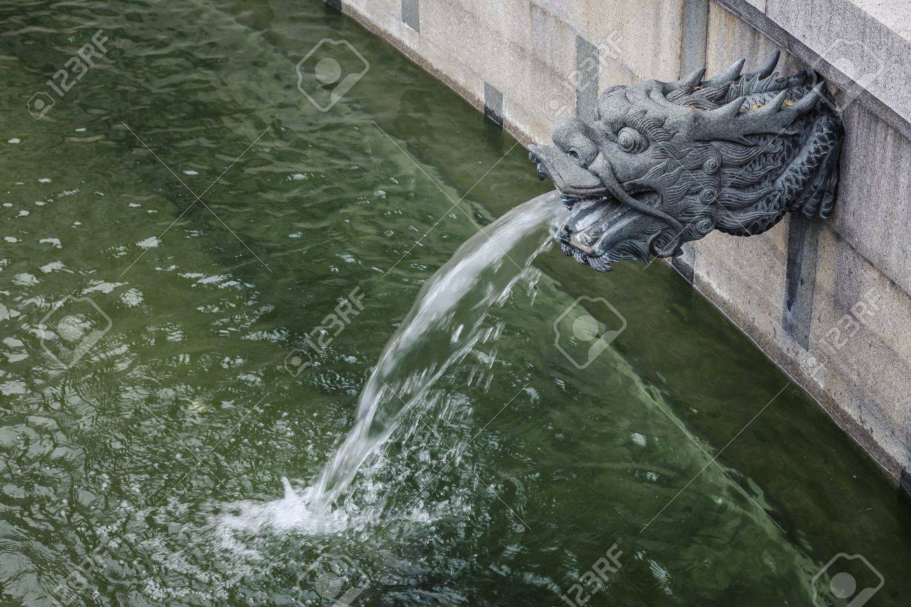 An Outdoor Ornamental Dragon Head Water Spout Spraying A Stream