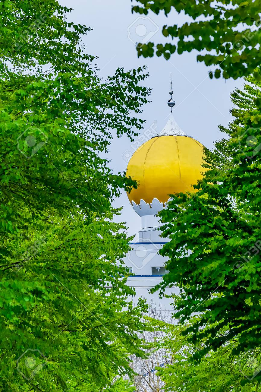 Golden globe roof architecture of a Sikh Temple seen from between the trees. Stock Photo - 58940688