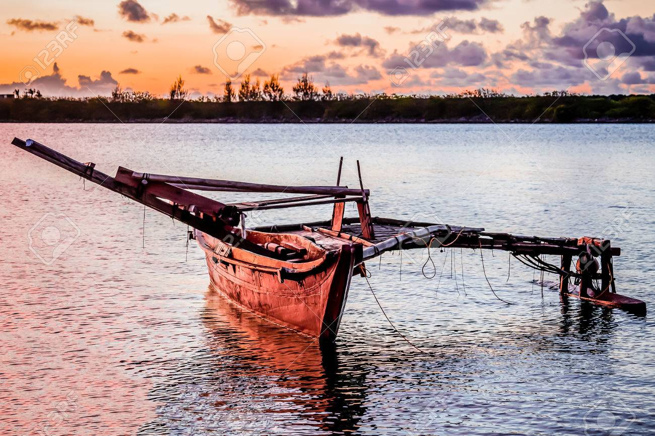 A wooden Micronesian canoe anchored in the bay at sunset. Stock Photo - 64068032