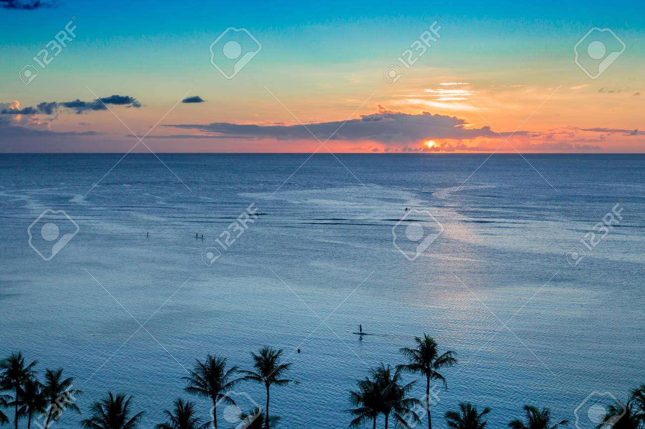 Paddle boarders enjoying a tropical island sunset . Stock Photo - 64068045