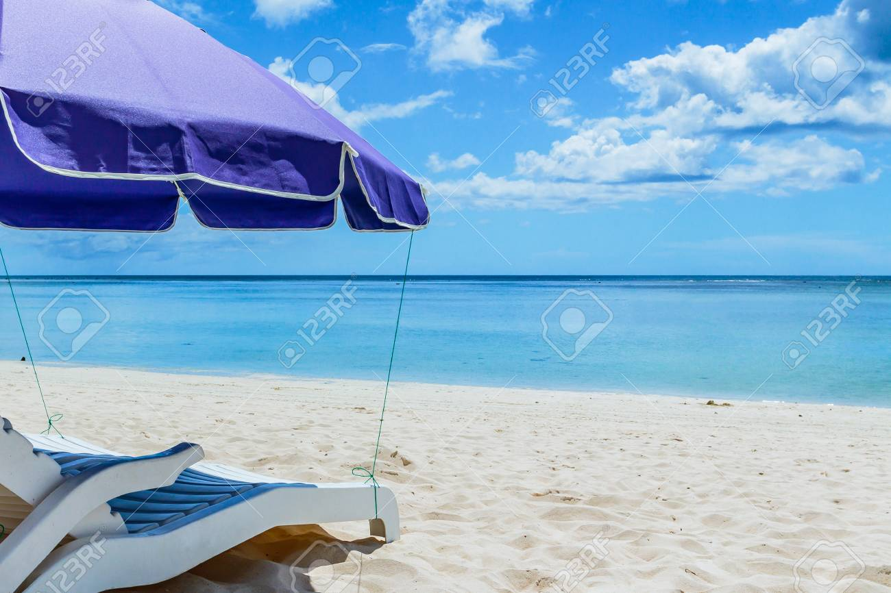 A pair of beach chairs under an umbrella on a deserted beach with white sand. Stock Photo - 64067451