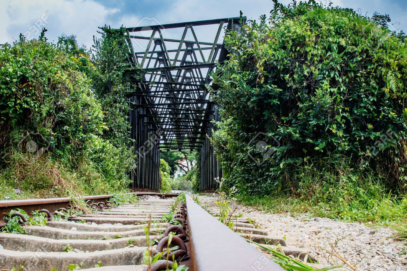 Close up of defunct railroad tracks leading up to a bridge. Stock Photo - 77487051