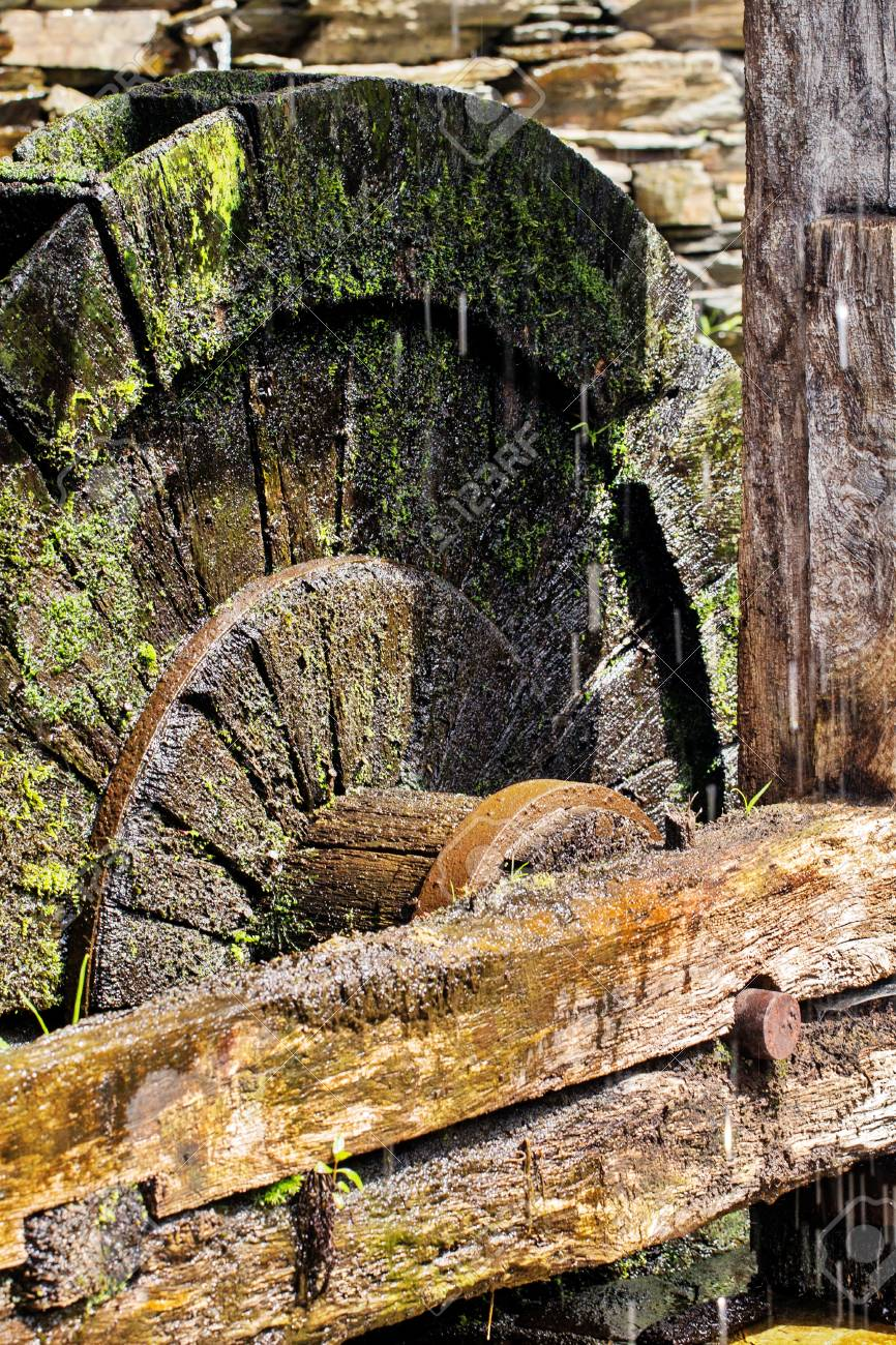 Fragment of an old wheel of a mill  The wet turned black wooden