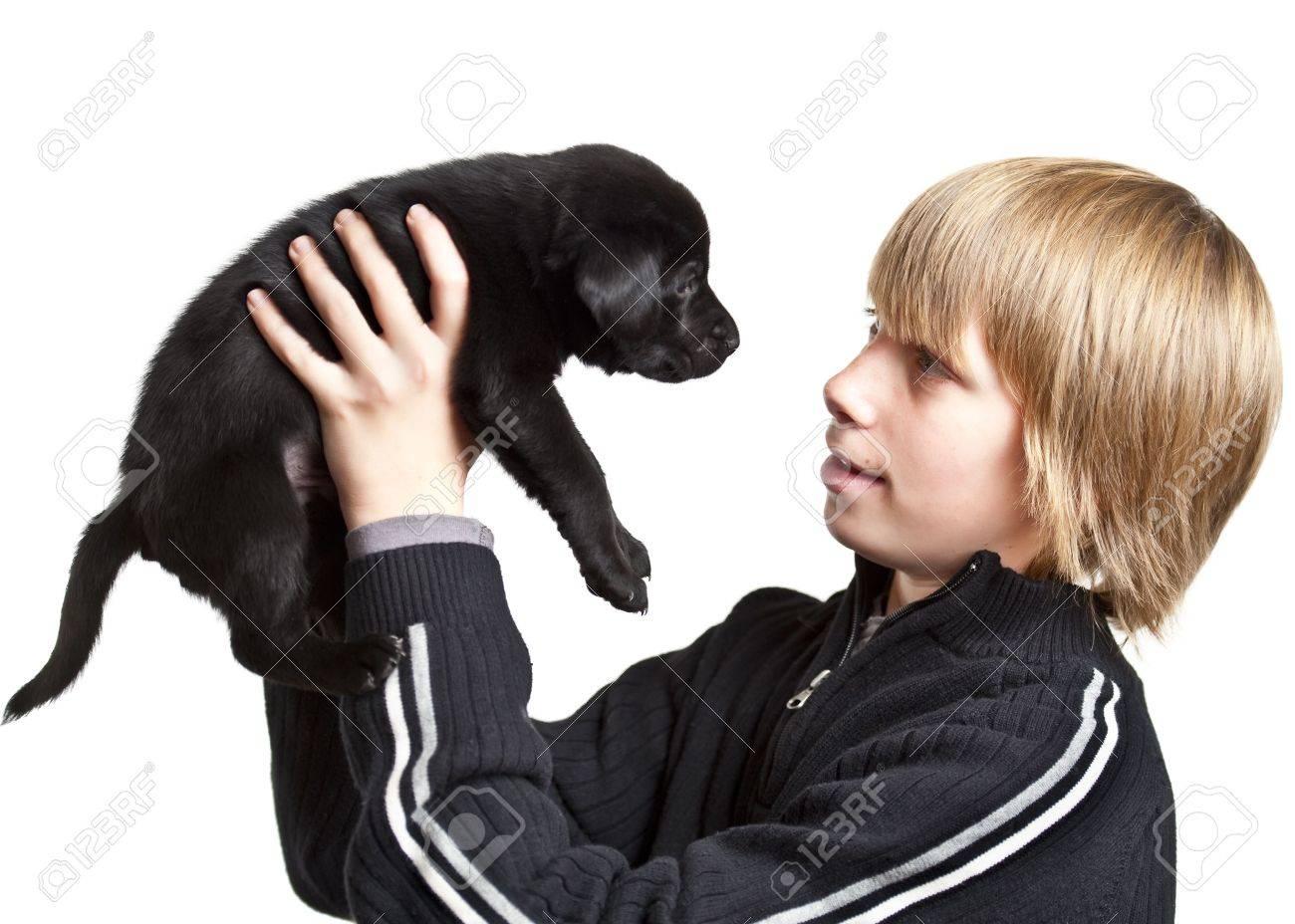 Teenager holding a black puppy dog. Image on white background Stock Photo - 6350257