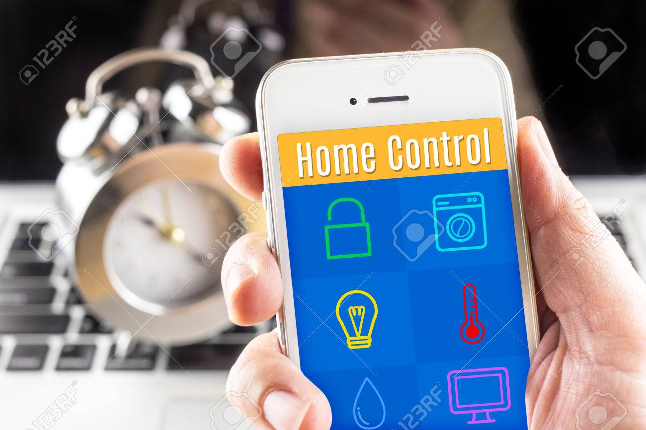 Smartphone Home Control hand holding smart phone with home control application with clock
