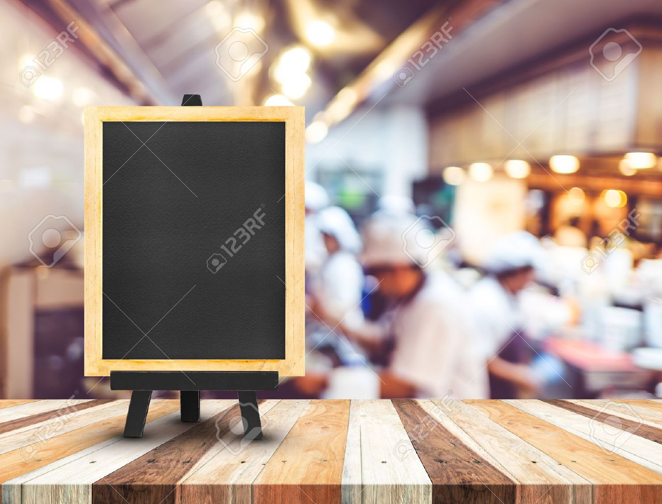 Restaurant Kitchen Background Blackboard Menu With Easel On Wooden Table With Blur Open Kitchen