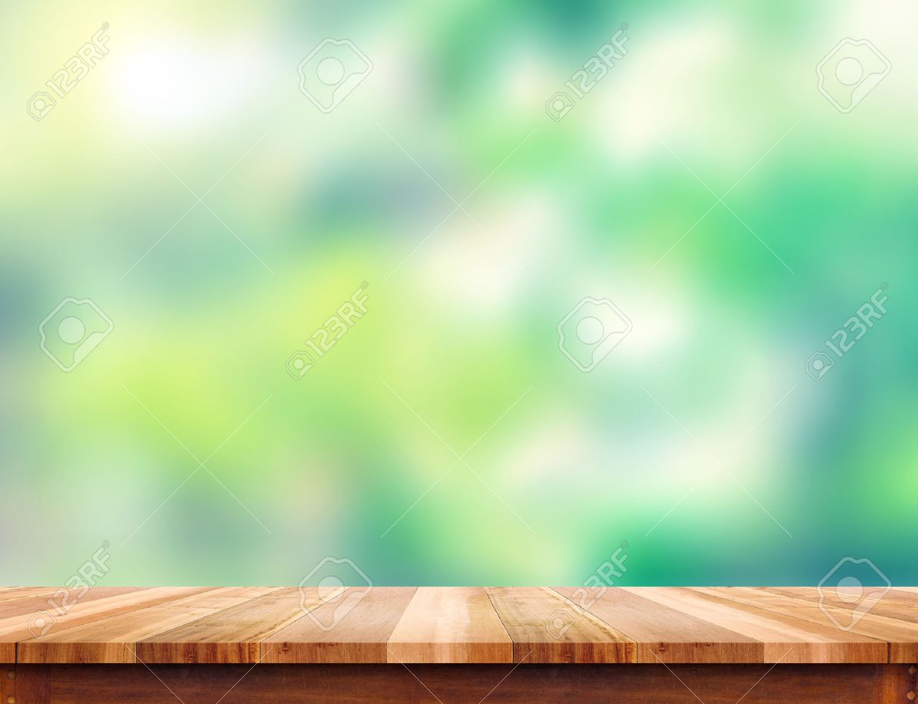 empty plank brown wood table top with blur green tree background