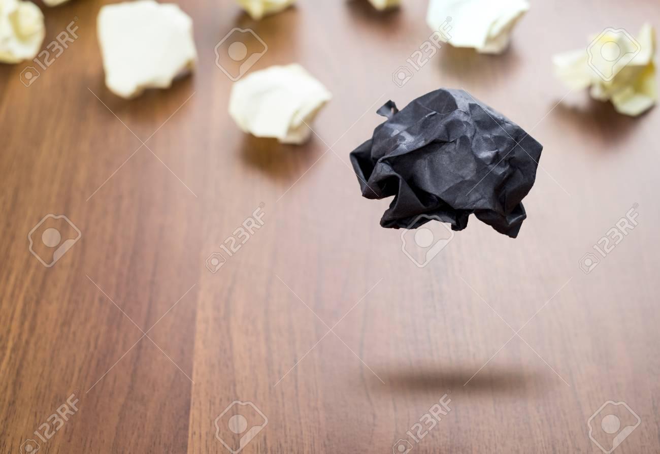 boule de papier noire et froissée flottant autour de la balle de