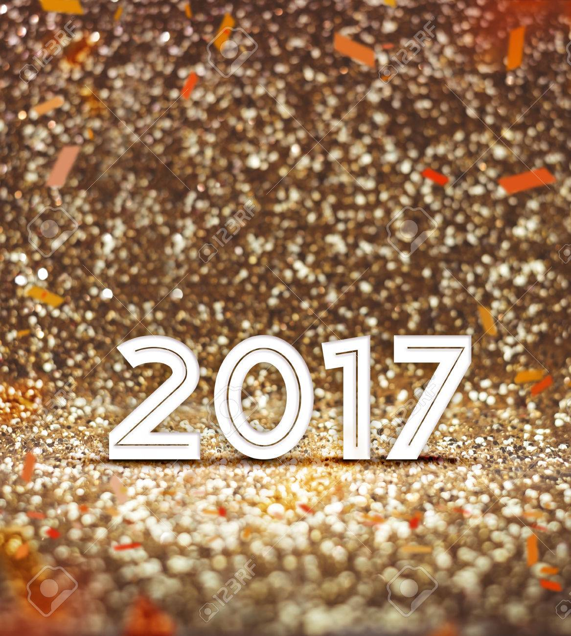 stock photo vintage filter happy new year 2017 year number with confetti at sparkling golden glitter background holiday greeting cardleave space for