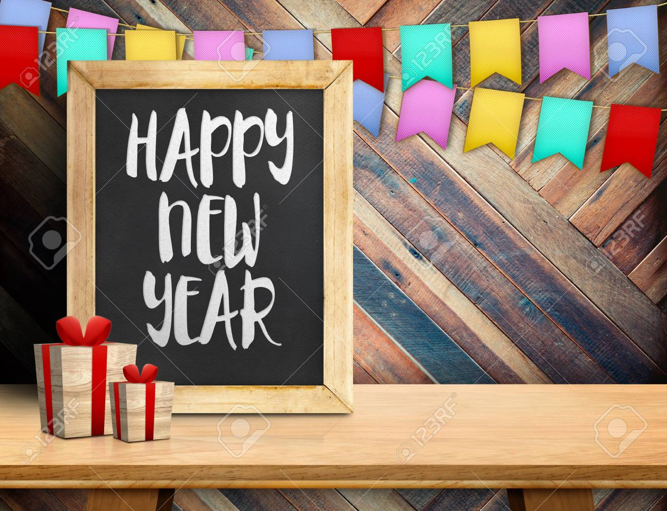 happy new year on blackboard with gift and colorful flag banner