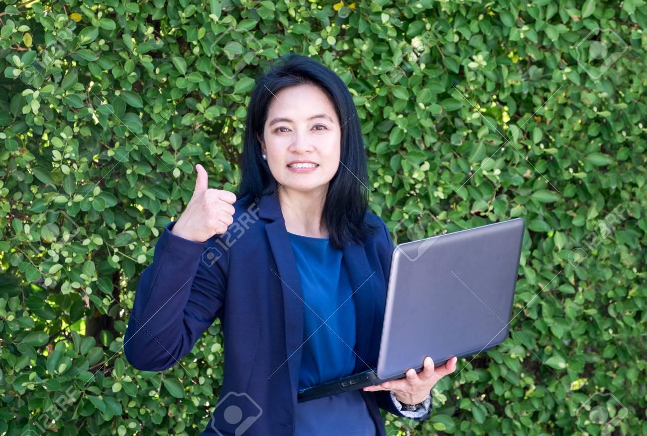 Parete Verde Ufficio : Colpo della donna di affari su e tenendo il computer portatile alla