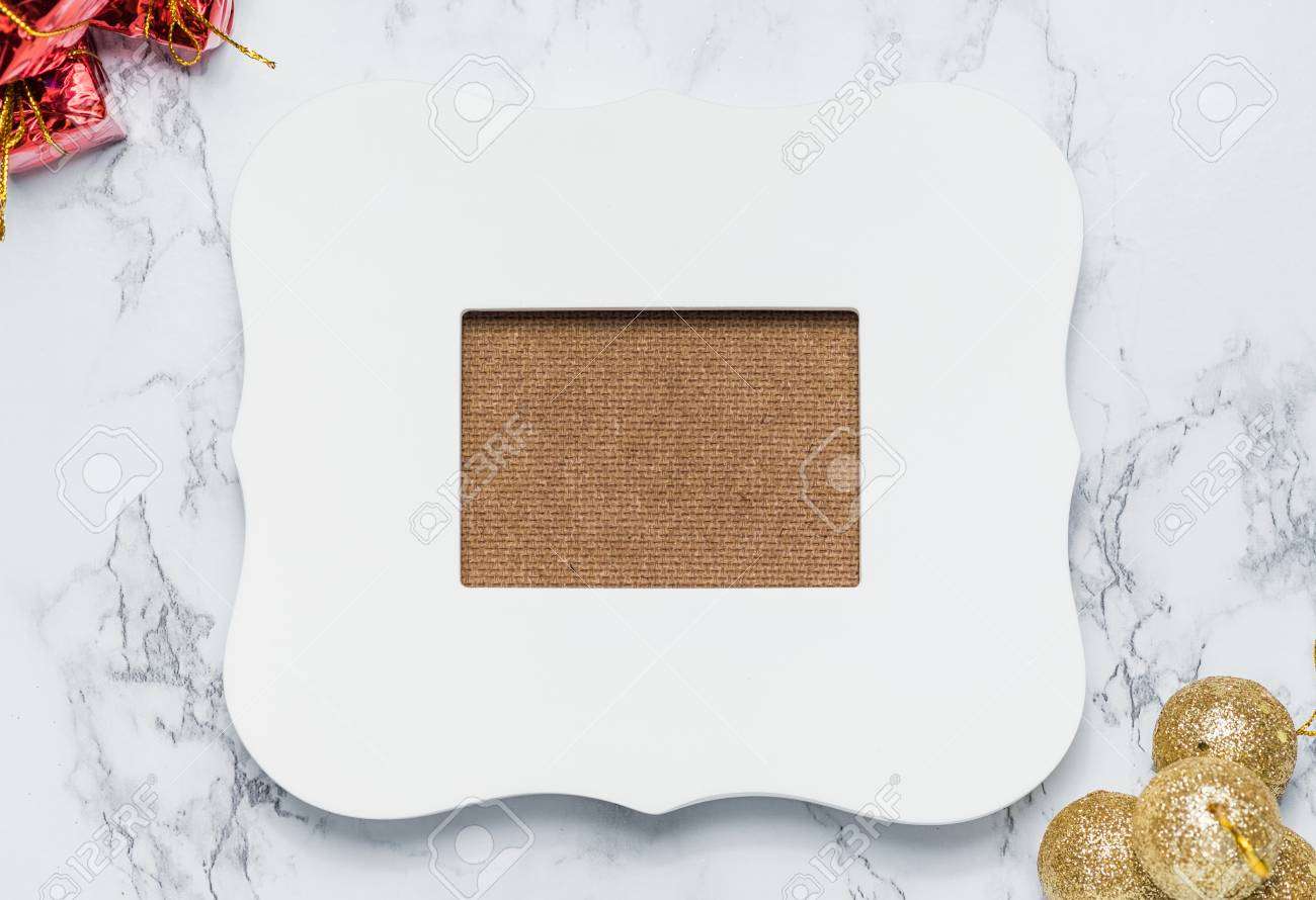 vintage white photo frame with red gift box and golden ball on