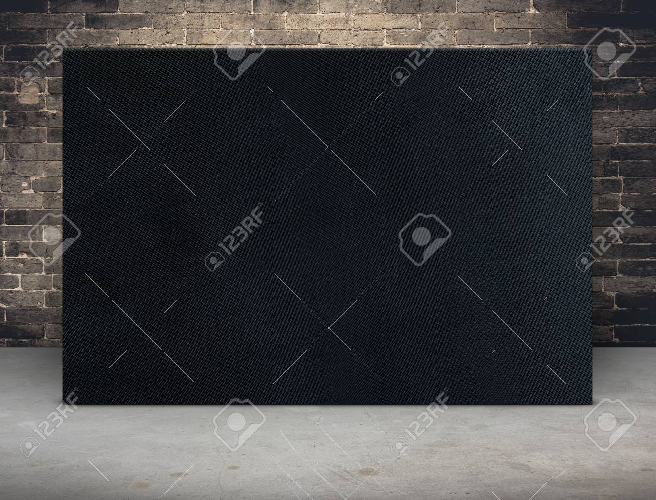 Blank black fabric canvas frame at grunge brick wall and concrete