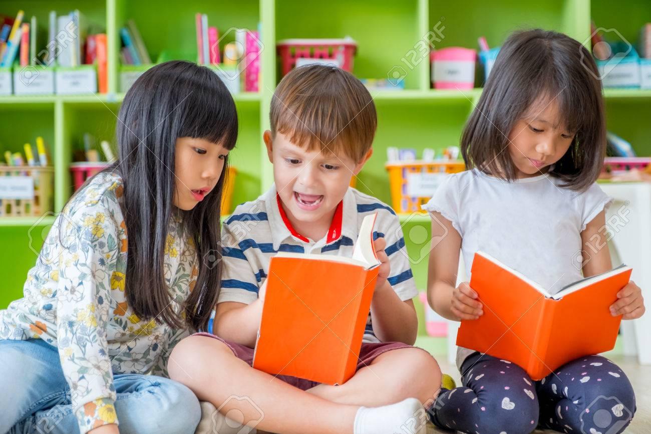 children sitting on floor and reading tale book in preschool stock