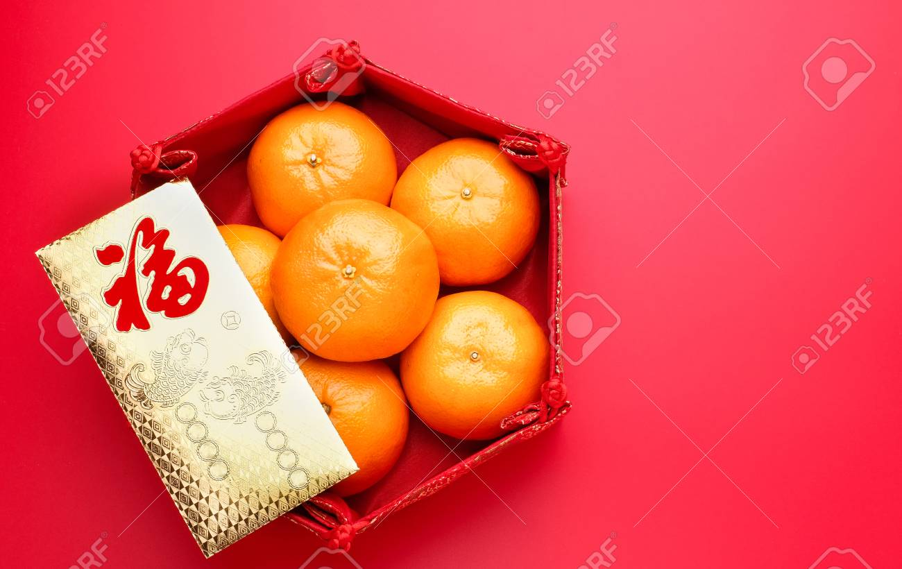 Group of orange tangerine in Chinese pattern tray and envelope packet ang pow on red table top. Chinese new year concep.Chinese Language on envelop is happiness,on ingot is wealthy - 93939705