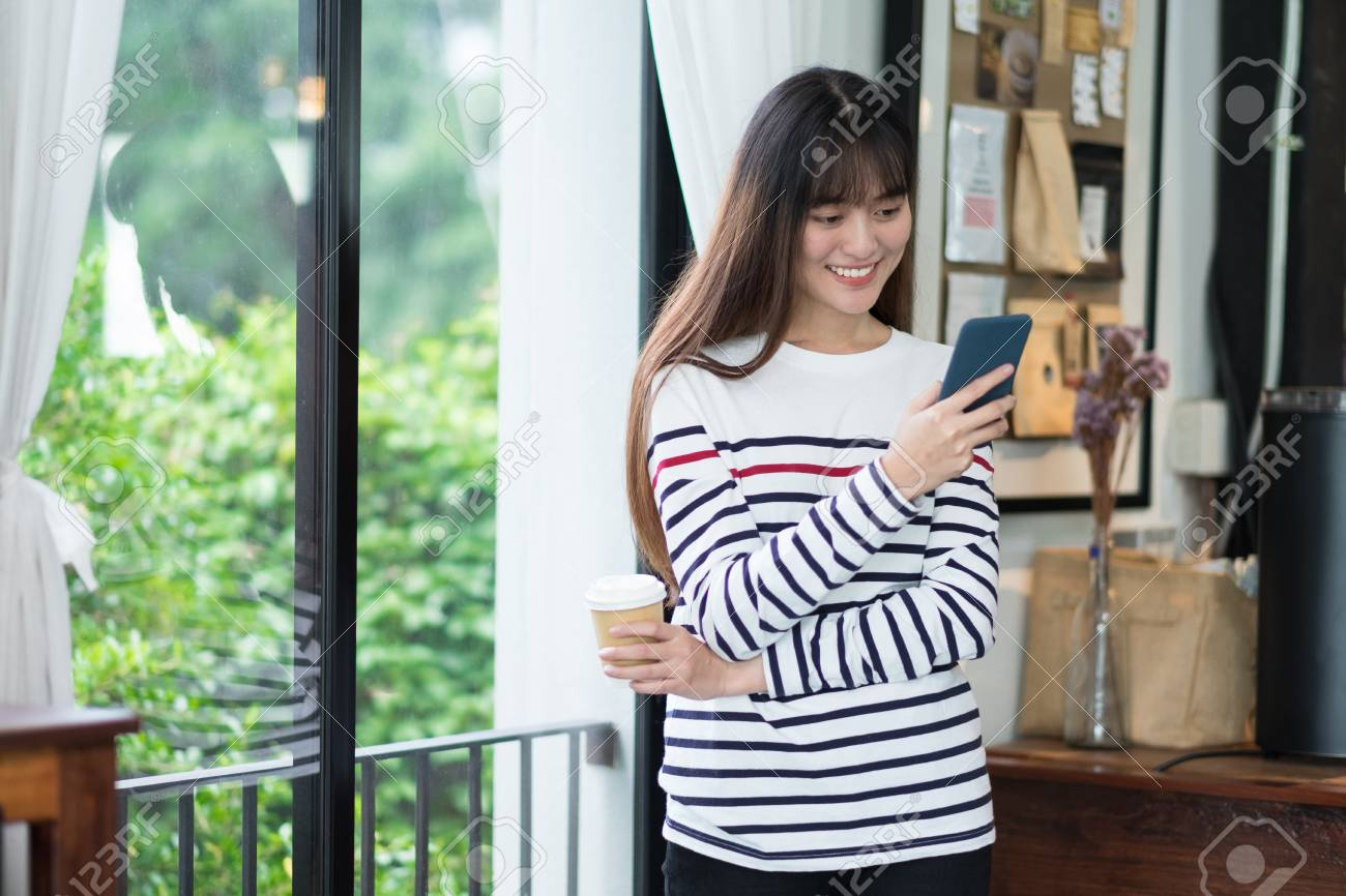 Asian Woman Talking On Mobile Phone Video Call And Standing At Stock Photo Picture And Royalty Free Image Image 103227919
