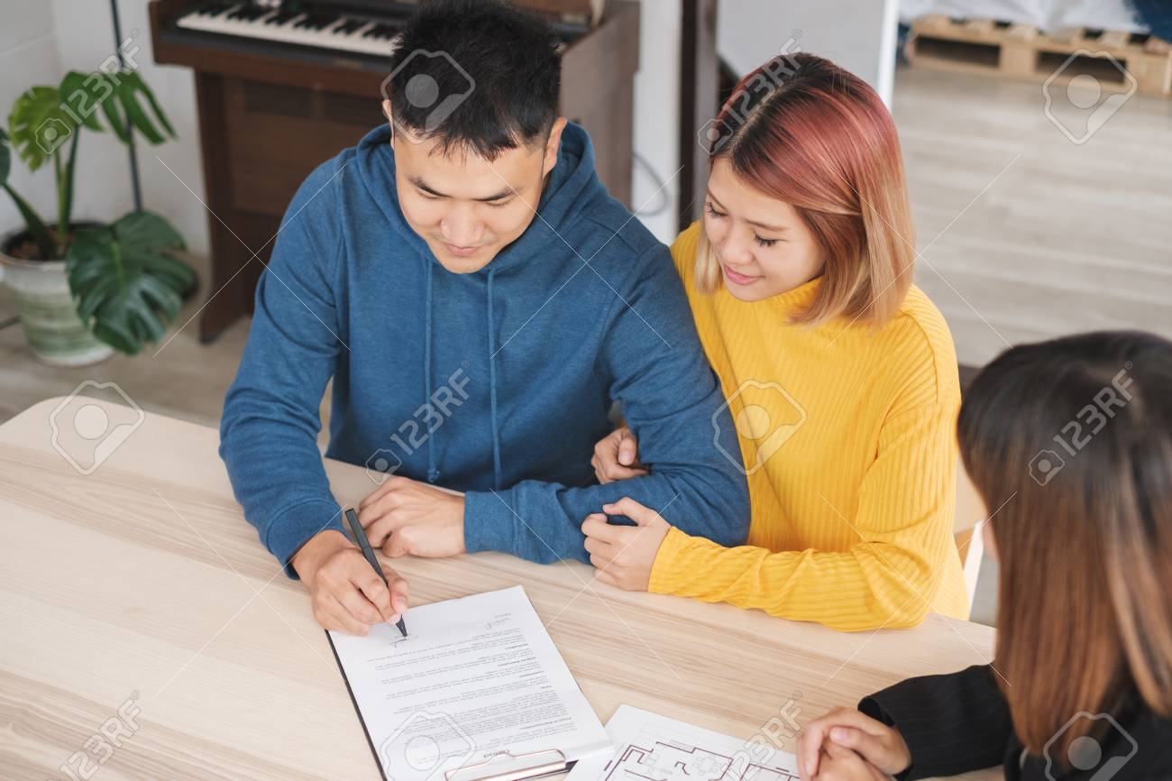 Asian happy couple sign contract buying new home with realtor agent with smiling face at new home.buying new house real estate - 112241516