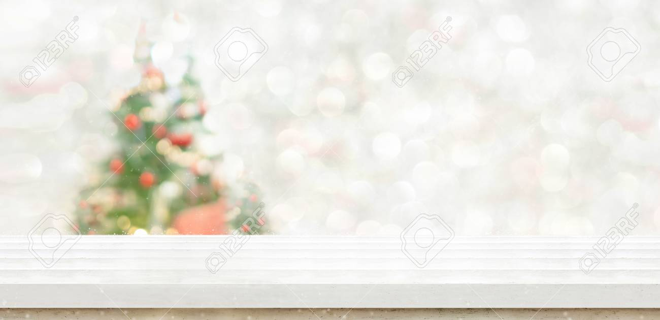 White Marble Table Top At Blur Bokeh Christmas Tree Decor With String Light Background When Show Falling Winter Holiday Greeting Card