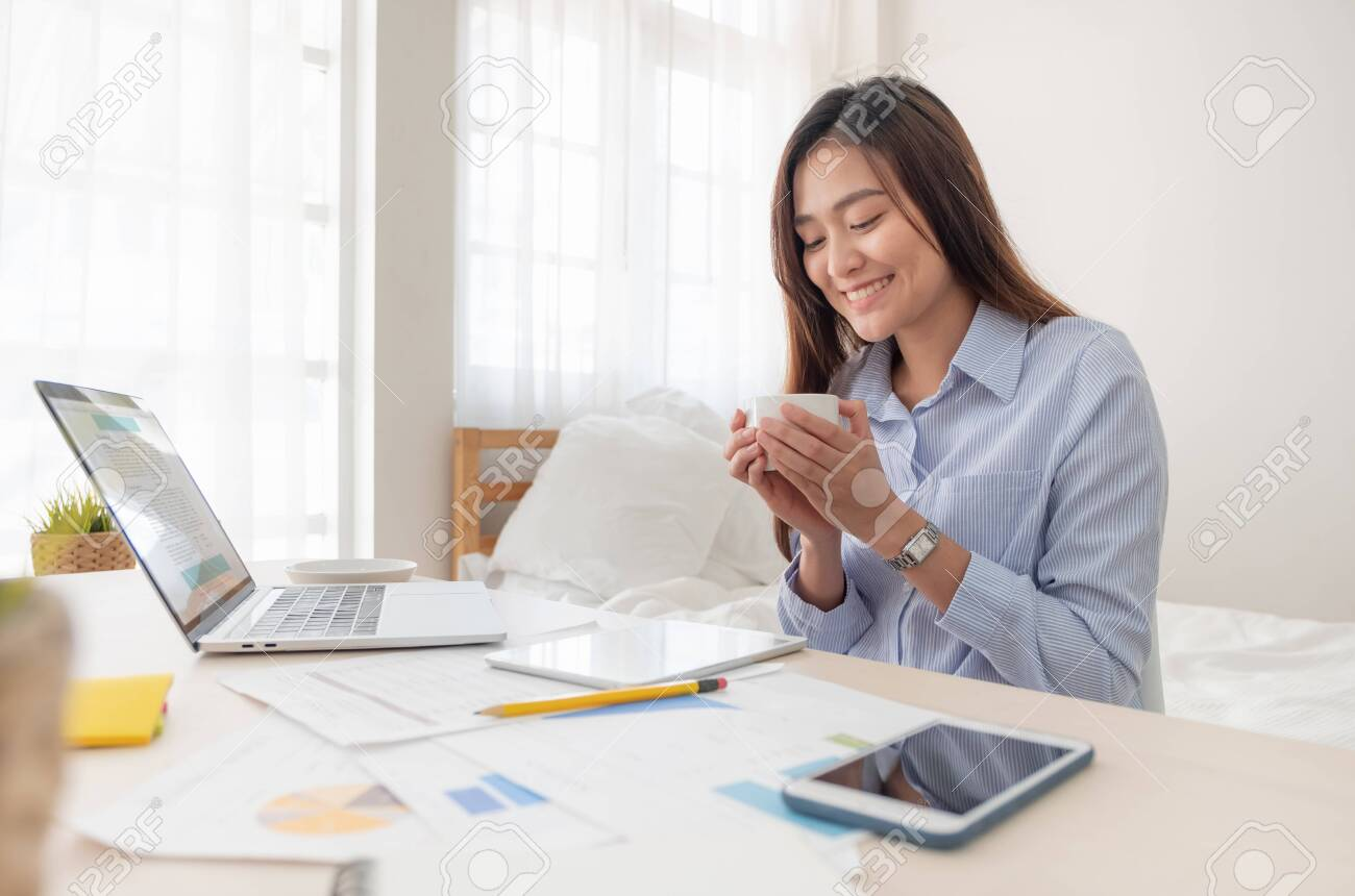 Asian businesswoman drinking coffee and while working with laptop on table in bedroom at home.Work at home concept.work from home concept - 129293184