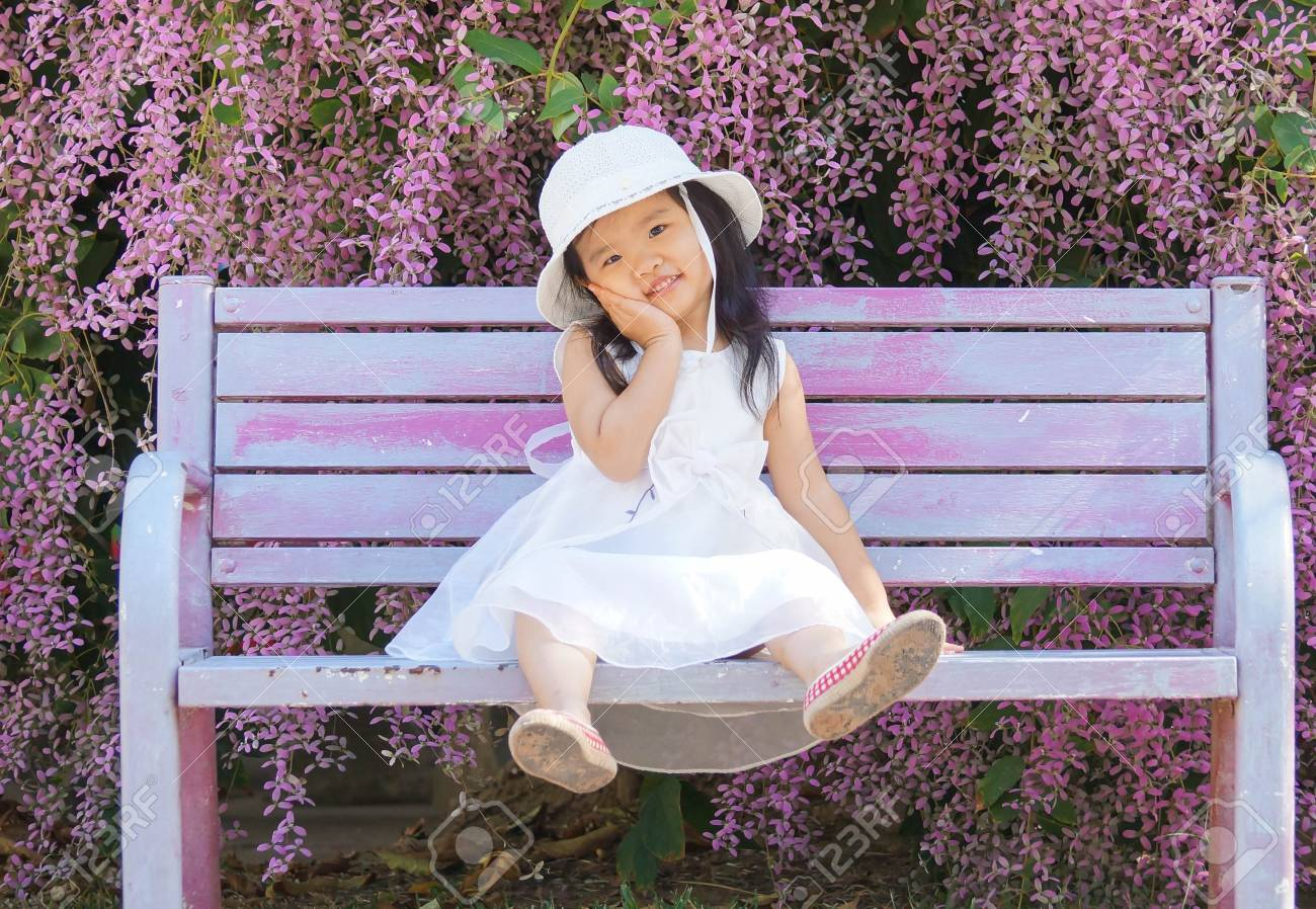 A Female Kid In A White Dress Sitting On A Bench With Beautiful