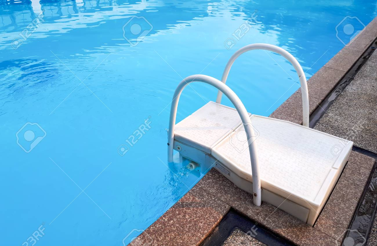 A swimming pool with a rail and a ladder