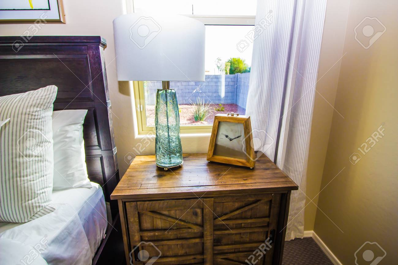 Glass Lamp And Clock On Wooden Nightstand