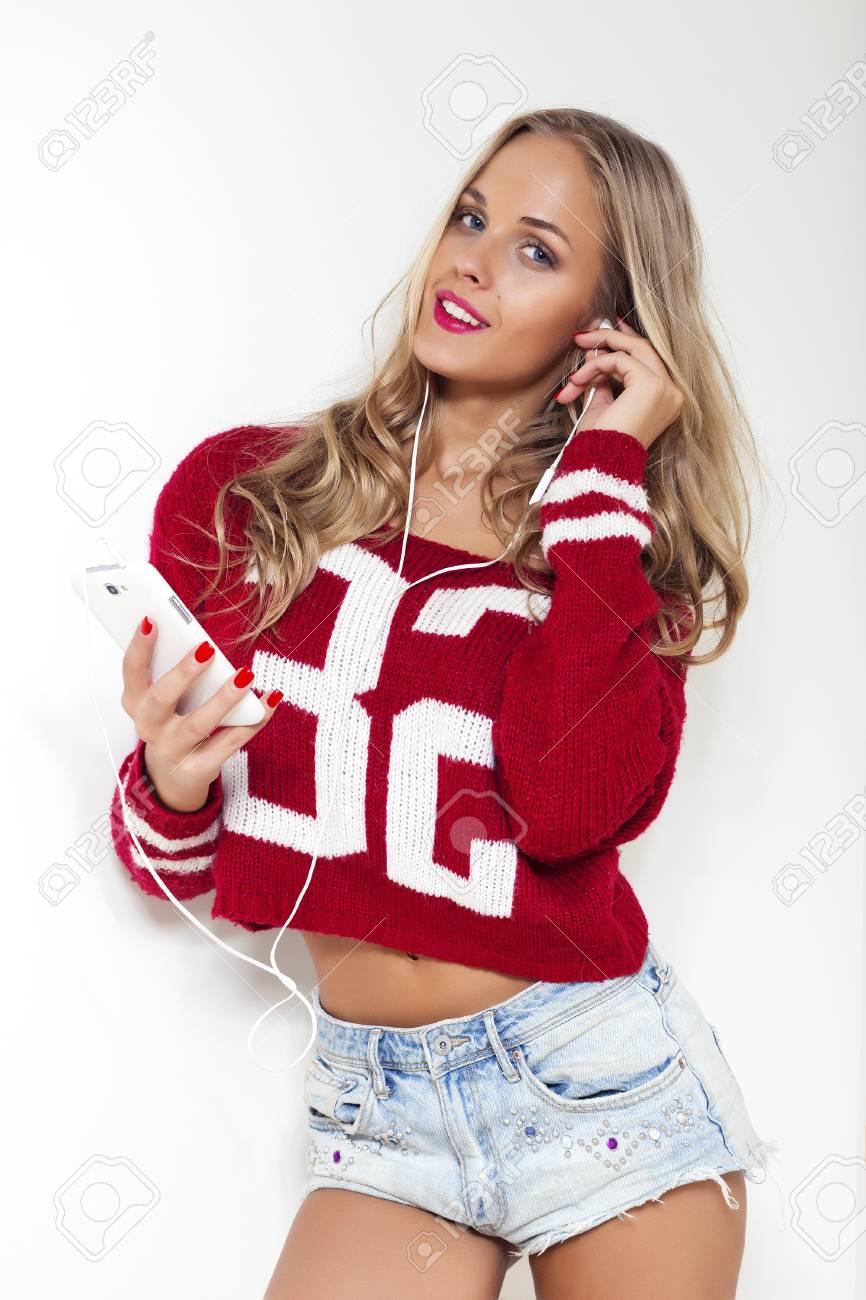 écouter Belle Et La Tenant Blonde De Rouge Femme Longs élégante Musique Cheveux Des Aux Bouclés Chemise Pose Téléphone Un Jean écouteurs Short En Portant 66axSqr