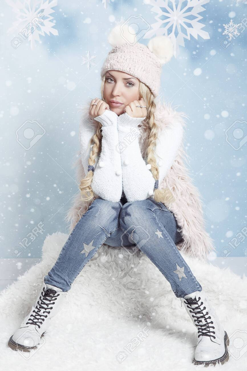 Portrait of a young blonde woman with long hair in winter clothes. Christmas-New year portrait on a soft blue background with snowflakes. - 136669421