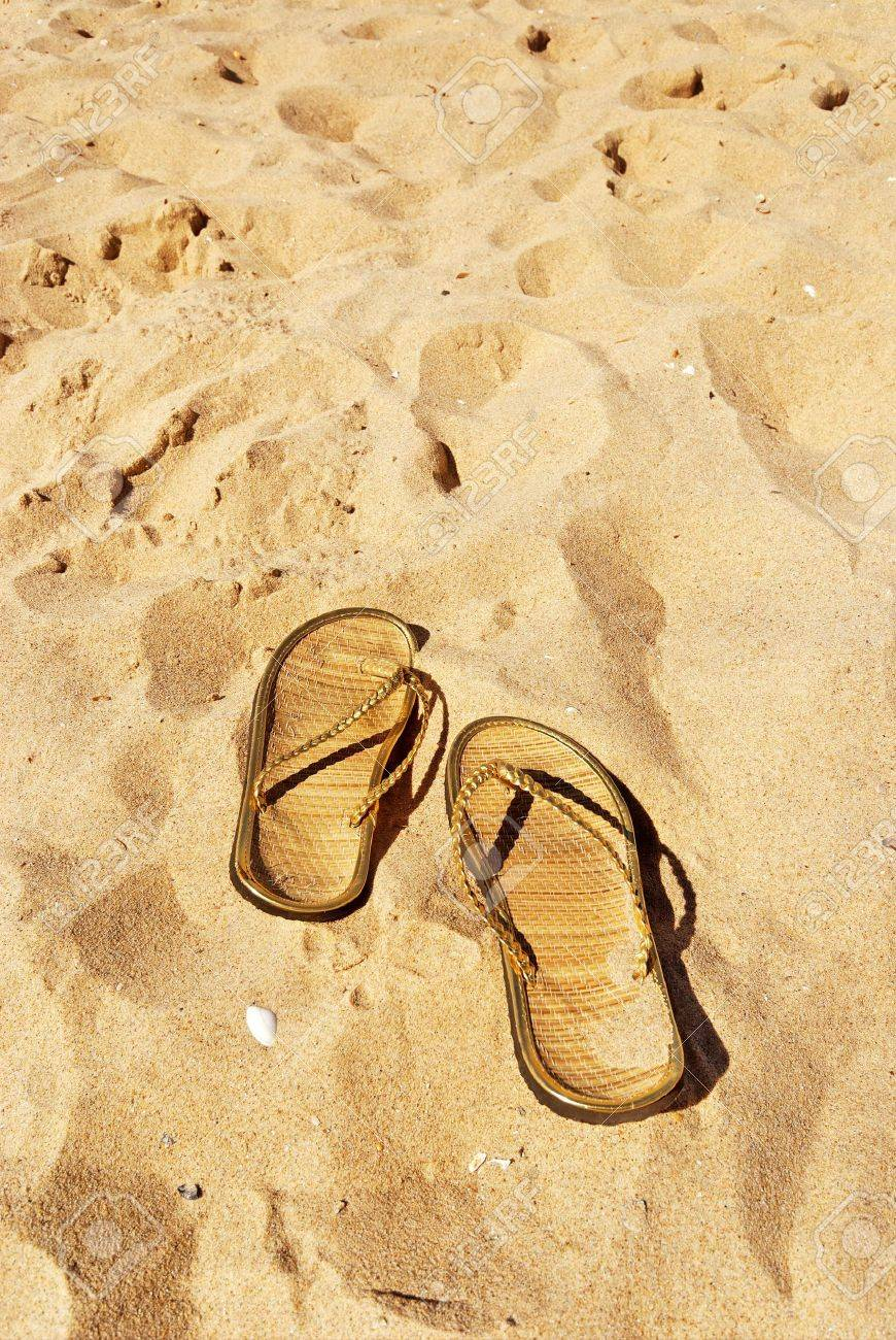 pair of golden slippers left in the sand with shells Stock Photo - 3527617