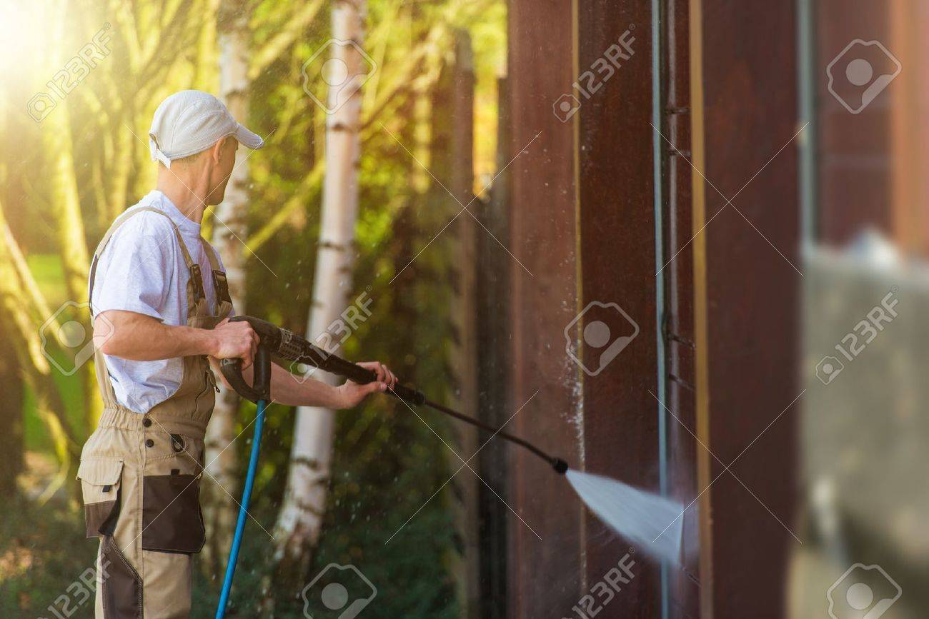 Garage Gate Water Cleaning. Garage Walls and Gate Powerful high Pressure Water Washing. Caucasian Worker Cleaning Building Elements. - 56892247