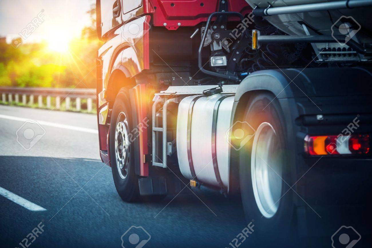 Red Semi Truck Speeding on a Highway. Tractor Closeup. Transportation and Logistics Theme. - 56892337