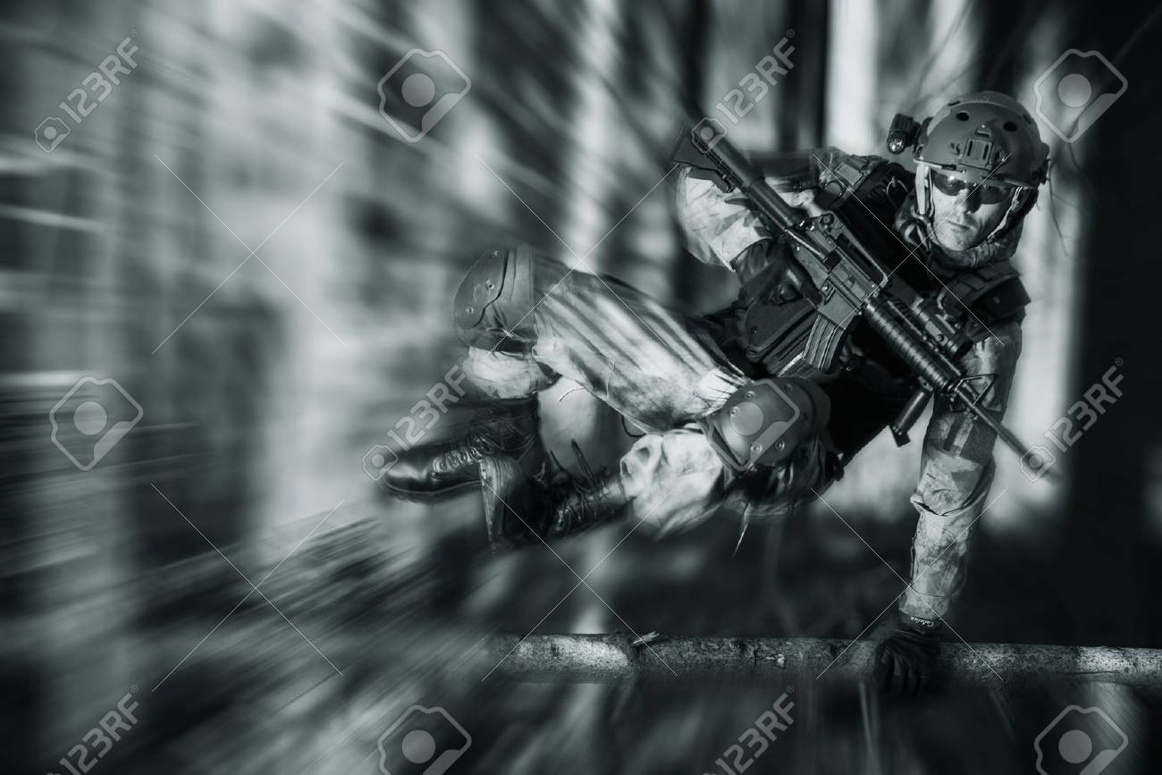Army Soldier in Action Jumping Over Fallen Tree. Military Concept. - 56892368