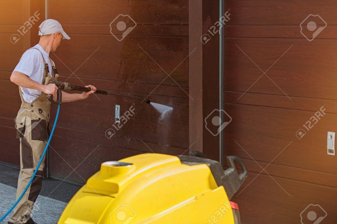 Garage Door Washing by High Pressured Water. Caucasian Men Cleaning Garage Doors. - 60767198
