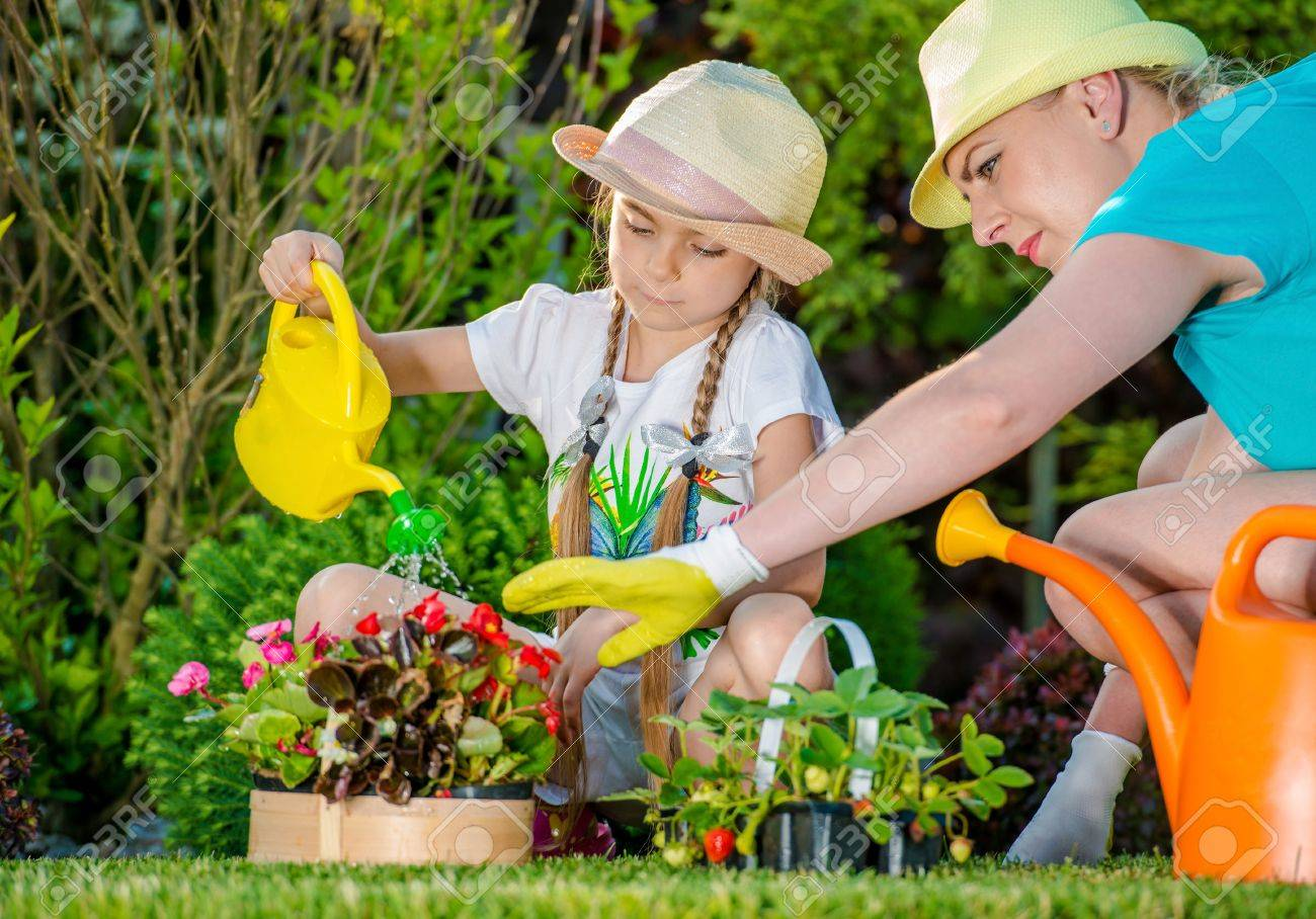 Mother And Daughter Working In Backyard Garden Girl Learning