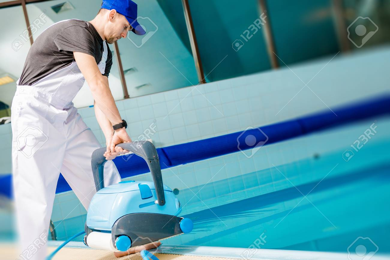 Swimming Pool Technician with Automated Pool Cleaner Preparing..
